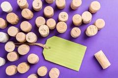 Tappi del sughero del vino con l'etichetta verde su fondo porpora Fotografia Stock Libera da Diritti