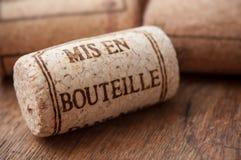 tappi il tappo del vino con testo - in bottiglia sulla tavola di legno Fotografia Stock