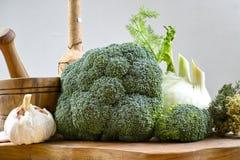 Tappi la bottiglia, il mortaio di legno verde oliva, le verdure verdi fresche, i broccoli, il finocchio, aglio Fotografia Stock