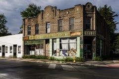 Tappning, övergett apotek med bluffbrunttegelsten och gräsplanporslintegelplattor royaltyfri fotografi