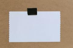 Tappning av anmärkningspapper på bruna bakgrunds- och kopieringsspecifikationer Arkivfoto