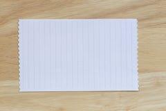 Tappning av anmärkningspapper på träbakgrunds- och kopieringsspecifikationer Royaltyfri Foto