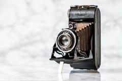 Tappning Azur Folding Camera på marmorbakgrund arkivbild