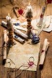 Tappning bläddrar, och stearinljus är den gamla scribe'sens arbetsplats Royaltyfria Bilder