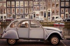 Tappning Citroen 2CV parkerade längs en kanal i Amsterdam Nederländerna Mars 2015 arkivfoton