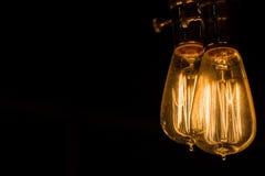 Tappning Edison Light Bulbs som hänger mot en svart bakgrund Arkivfoto