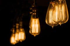 Tappning Edison Light Bulbs som hänger mot en svart bakgrund Fotografering för Bildbyråer