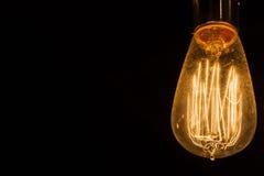 Tappning Edison Light Bulbs som hänger mot en svart bakgrund arkivbild