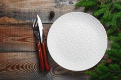 Tappning eller lantlig jul bordlägger inställningen från över Den eleganta tomma vita plattan, bestick och naturliga sörjer trädf royaltyfria foton