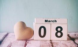 Tappning filtrerade bild av den träkalendern för mars 8, bredvid vit hjärta på den gamla lantliga tabellen Selektivt fokusera Royaltyfri Fotografi