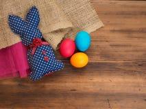 Tappning, lantlig bakgrund med en leksakkanin och kulöra ägg på bakgrund av säckväv och den gamla trätabellen Top beskådar Royaltyfria Bilder