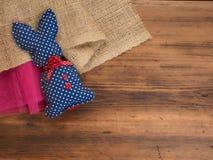 Tappning, lantlig bakgrund med en leksakkanin på en bakgrund av säckväv och gammal trätabell Top beskådar Royaltyfri Bild
