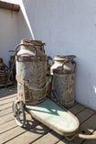 Tappning mjölkar mjölkkannor med vagnen Royaltyfri Fotografi
