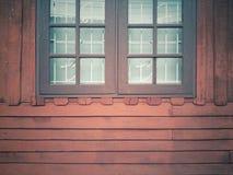 Tappning och dubbla fönster av bruna trähus Arkivfoto