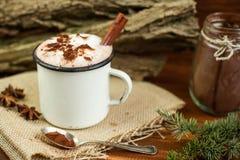 Tappning rånar av varm choklad med kanelbruna pinnar över lantlig bakgrund Arkivfoto