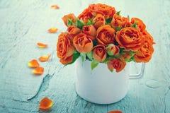 Tappning redigerade orange rosor i en vit kopp royaltyfria foton