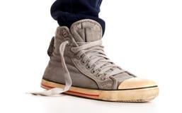 Tappning som ser gymnastikskor och riven sönder jeans Arkivfoton