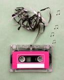 Tappning som ser kassetten för det magnetiska bandet för ljudsignal musikinspelning med sånganmärkningen, blåser ut Arkivbild