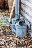 Tappning som två bevattnar cans som står utanför i blad Arkivbilder