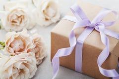 Tappning steg blommor och gåvaasken med bandet på den ljusa tabellen Hälsningkort för födelsedag-, kvinnors eller moderdag Royaltyfri Fotografi