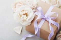 Tappning steg blommor och gåvaasken med pilbågebandet på den ljusa tabellen Hälsningkort för födelsedag-, kvinnas eller moderdag Royaltyfria Foton