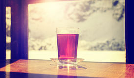 Tappning stiliserade exponeringsglas av varmt te på trätabellen Royaltyfri Fotografi