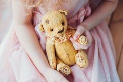 Tappning Teddy Bear i händer för liten flicka` s Fotografering för Bildbyråer
