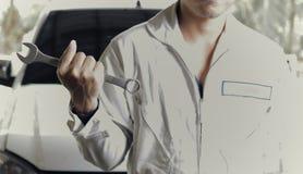 Tappning tonad bild av den yrkesmässiga unga mekanikermannen i enhetlig innehavskiftnyckel mot bilen på reparationsgaraget royaltyfri fotografi