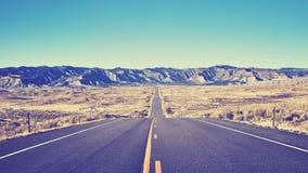 Tappning tonade ökenasfaltvägen, det rörande framåtriktat begreppet, USA Royaltyfria Bilder