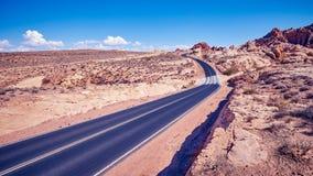 Tappning tonade den panorama- bilden av en scenisk väg Royaltyfri Foto