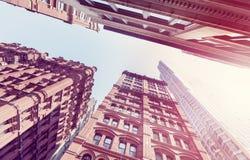 Tappning tonade gammalt och nybyggen i Manhattan på solnedgången, NYC Arkivfoton