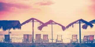 Tappning tonade strandstolar, och paraplyer på solnedgången, semestrar bac Arkivbilder