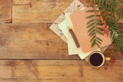 tappninganteckningsbok, gammalt papper och träblyertspenna bredvid koppen kaffe över trätabellen ordna till för modell Royaltyfri Foto