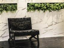 Tappningarmstol i inre vardagsrum med väggmarmor för kopieringsutrymme inre minsta för möblemang Arkivbild