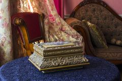 Tappningask Antik casket på tabellen mot bakgrunden av en klassisk inre som består av gardiner och soffan för en stol royaltyfria foton