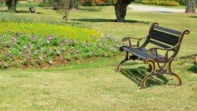 Tappningbänk i blommaträdgård Arkivfoto