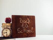 Tappningböcker, gammal klocka, blyertspennor, rött äpple och svart tavla arkivfoto