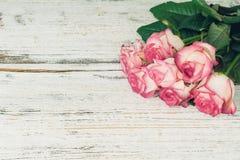 Tappningbakgrund med den rosa rosbuketten på den vita tabellen arkivfoton