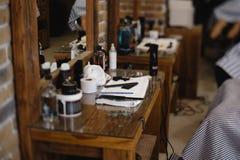 Tappningbarberare- eller rakapparathjälpmedel på trätabellen i en frisersalong arkivfoton