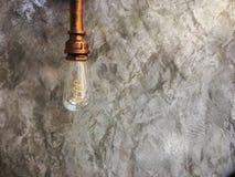 Tappningbelysninglampan hänger framme av cementväggen på vinden royaltyfri fotografi