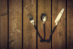Tappningbestick - gaffel, sked och kniv som fläktas på Wood Backgroun Arkivfoton