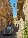 Tappningbil som korsar en typisk gata av sydliga Italien Royaltyfri Foto