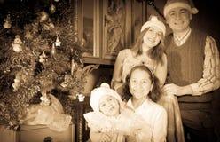 Tappningbild av den lyckliga familjen med julgranen Royaltyfri Bild
