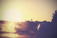 Tappningbild av vägen med bilar i rörelse mot solen Fotografering för Bildbyråer