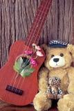 Tappningbjörnen leker med ukulelet Arkivbild
