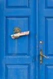 Tappningblåtten trädubbel dörr med bronsknackaren och tidningar royaltyfria foton