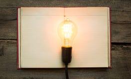 Tappningbok och ljus kula på den wood tabellen Royaltyfria Foton