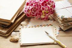 Tappningbokstäver, böcker och bukett av rosa hortensiablommor Royaltyfria Bilder