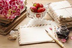 Tappningbokstäver, böcker och bukett av rosa hortensiablommor Royaltyfria Foton
