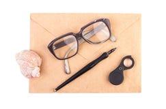 Tappningbokstav, penna och exponeringsglas på en vit Arkivfoto